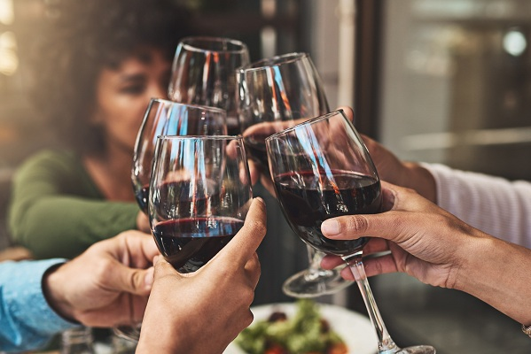 Shot of a group of cheerful young friends having a celebratory toast with wine at dinner inside of a restaurant